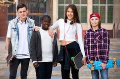 Adolescentes con los monopatines que presentan en plaza Foto de archivo