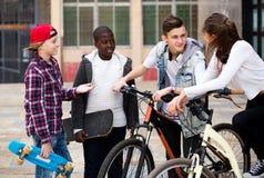 Adolescentes con los monopatines que presentan en plaza Fotos de archivo libres de regalías