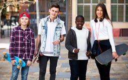 Adolescentes con los monopatines que presentan en plaza Fotos de archivo