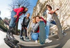 Adolescentes con los patines y los monopatines en línea Imagenes de archivo