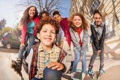 Adolescentes con los patines y los monopatines en línea Foto de archivo libre de regalías
