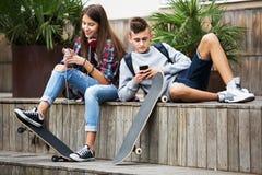 Adolescentes con los smarthphones Imagen de archivo