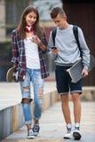 Adolescentes con los smarthphones Imagen de archivo libre de regalías