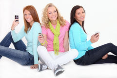 Adolescentes con los teléfonos celulares Foto de archivo
