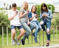 Adolescentes con los teléfonos en parque Foto de archivo