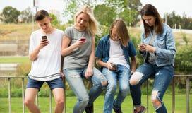 Adolescentes con los teléfonos en parque Foto de archivo libre de regalías