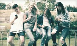 Adolescentes con los teléfonos en parque Fotografía de archivo libre de regalías