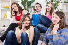 Adolescentes con los teléfonos móviles Imagen de archivo