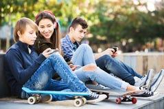 Adolescentes con los teléfonos móviles Foto de archivo libre de regalías