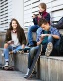 Adolescentes con los teléfonos móviles Imagenes de archivo