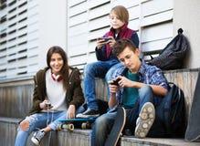 Adolescentes con los teléfonos móviles Imágenes de archivo libres de regalías
