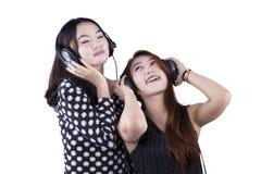 Adolescentes con música que escucha de los auriculares Foto de archivo libre de regalías
