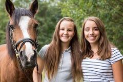Adolescentes con su potro Foto de archivo libre de regalías
