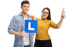 Adolescentes con una L-muestra y una llave del coche Imágenes de archivo libres de regalías