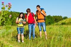 Adolescentes confundidos que olham no mapa Fotos de Stock Royalty Free