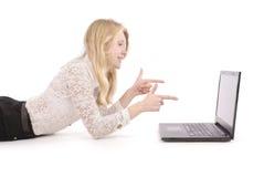 Adolescentes consideravelmente novos com o portátil que encontra-se no assoalho Imagem de Stock