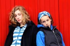 Adolescentes contra la pared roja Fotos de archivo libres de regalías