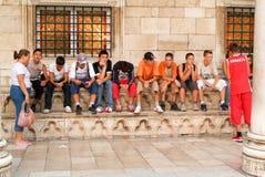 Adolescentes croatas que se sientan en fila en Dubrovnik Foto de archivo libre de regalías