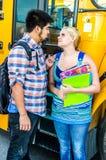 Adolescentes da idade escolar que esperam para obter no ônibus fotografia de stock royalty free