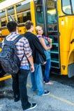 Adolescentes da idade escolar que esperam para obter no ônibus fotos de stock royalty free