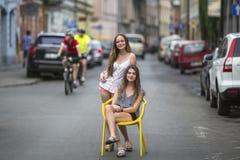 Adolescentes dans la rue de la vieille ville Une fille s'assied sur la chaise sur la route, la deuxième fille était derrière elle Image stock