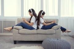 Adolescentes das irmãs com telefone esperto e música de escuta dos fones de ouvido e ommunicate em redes sociais imagem de stock royalty free