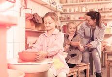 Adolescentes de ayuda del profesor en la fabricación de la cerámica durante artes y craf Imagen de archivo libre de regalías