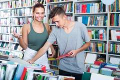 Adolescentes de la muchacha y del muchacho en librería Foto de archivo