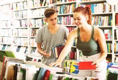 Adolescentes de la muchacha y del muchacho en librería Imagen de archivo