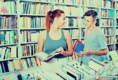 Adolescentes de la muchacha y del muchacho en librería Foto de archivo libre de regalías