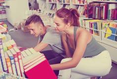 Adolescentes de la muchacha y del muchacho en librería Imagen de archivo libre de regalías