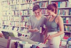 Adolescentes de la muchacha y del muchacho en librería Fotografía de archivo