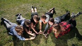 Adolescentes de la visión superior en círculo usando los teléfonos en parque metrajes