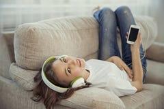 Adolescentes de las hermanas con el teléfono elegante y la música que escucha de los auriculares y ommunicate en redes sociales Imágenes de archivo libres de regalías