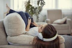 Adolescentes de las hermanas con el teléfono elegante y la música que escucha de los auriculares y ommunicate en redes sociales Imagen de archivo