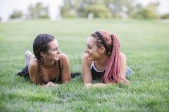 adolescentes de los inconformistas que sonríen el uno al otro en el parque Foto de archivo libre de regalías