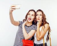Adolescentes de los mejores amigos junto que se divierten, presentación emocional en el fondo blanco, sonrisa feliz de los bestie Imagen de archivo libre de regalías