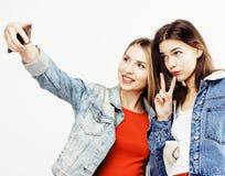 Adolescentes de los mejores amigos junto que se divierten, presentación emocional en el fondo blanco, sonrisa feliz de los bestie Imágenes de archivo libres de regalías