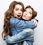 Adolescentes de los mejores amigos junto que se divierten, presentación emocional en el fondo blanco, sonrisa feliz de los bestie Foto de archivo
