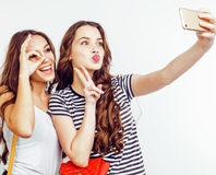 Adolescentes de los mejores amigos junto que se divierten, presentación emocional en el fondo blanco, sonrisa feliz de los bestie Fotos de archivo