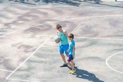 Adolescentes de los muchachos con una bola en la cancha de básquet Fotos de archivo