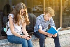 Adolescentes de los niños, libro de lectura de la rotura usando smartphone Fotografía de archivo