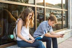 Adolescentes de los niños, libro de lectura de la rotura y smartphone con Imágenes de archivo libres de regalías