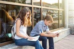 Adolescentes de los niños, libro de lectura y smartphone con Fotos de archivo libres de regalías