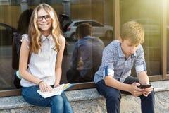 Adolescentes de los niños, libro de lectura y smartphone con Imagen de archivo