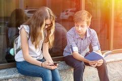 Adolescentes de los niños, libro de lectura y smartphone con Foto de archivo