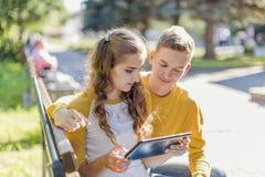 Adolescentes de los pares en un banco Foto de archivo libre de regalías