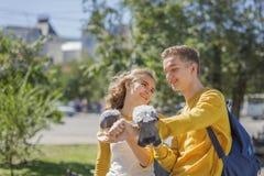 Adolescentes de los pares que alimentan palomas en la calle de la ciudad Fotos de archivo libres de regalías