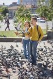 Adolescentes de los pares que alimentan palomas en la calle de la ciudad Foto de archivo
