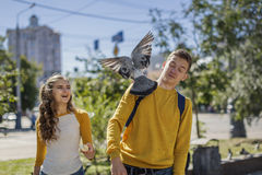 Adolescentes de los pares que alimentan palomas en la calle de la ciudad Fotografía de archivo libre de regalías